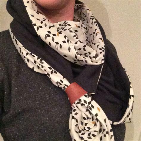 driehoek sjaal met aan de punten een leren bandje zwarte stof  tricot en de andere stof