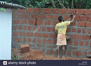 A mason at work building a wall of laterite blocks/stones ...