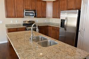 pictures of kitchen islands with sinks a closeup view of the granite slab countertop and the undermount stainless steel sink in the