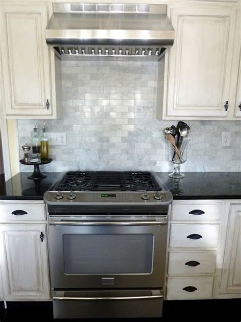 marble  backsplash dark counters white cabinets