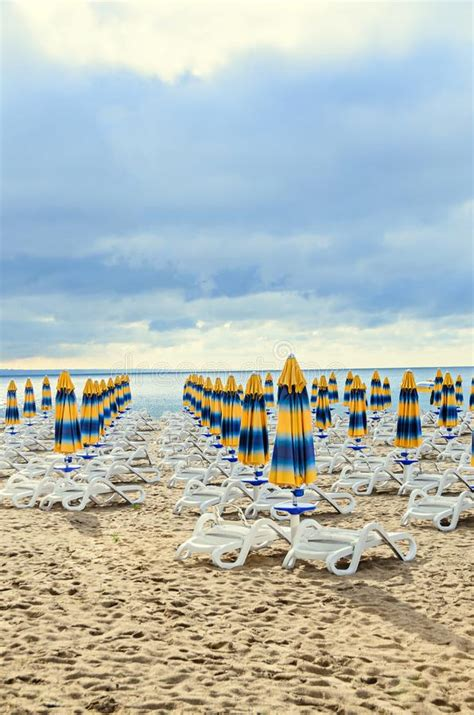 colored stripped sun umbrellas golden sand and sunbeds stock of relaxation