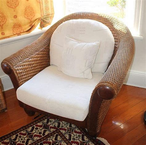 pair of large wicker tub chairs with white cushion