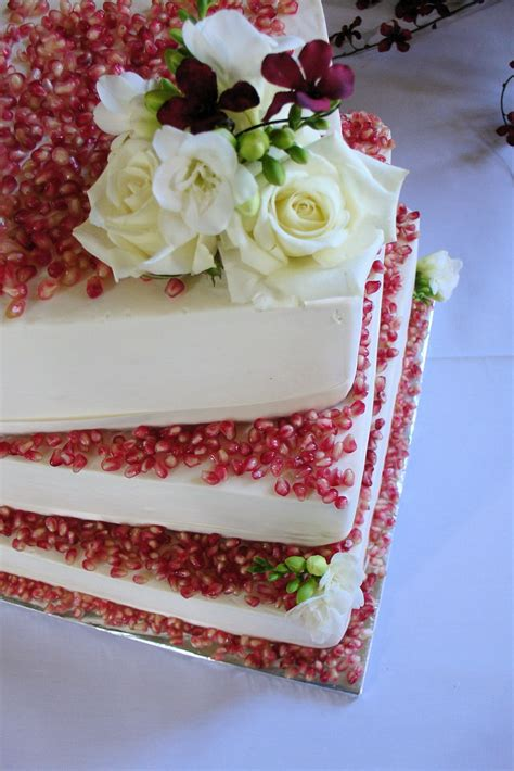 red velvet wedding cake decorated  pomegranate  whi
