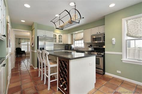 a lovely kitchen with traditional white cabinets a terracotta kitchen floor and a hanging pot