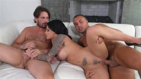 A Sexy Minx Is Posing For Two Men Naked On The Sofa In A Threesome