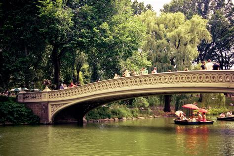 Central Park Boat Dock by Umbrellas And Row Boats Bow Bridge Ny