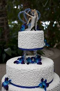 top tier of a royal blue wedding cake decorated with white ...