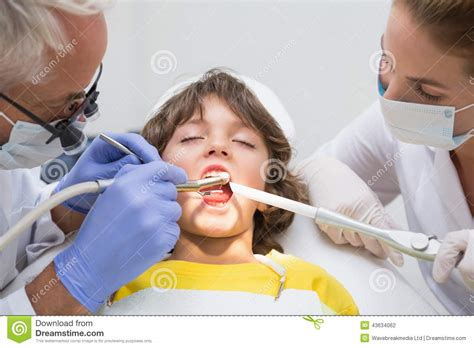 Pediatric Assistant by Pediatric Dentist And Assistant Examining A Boys