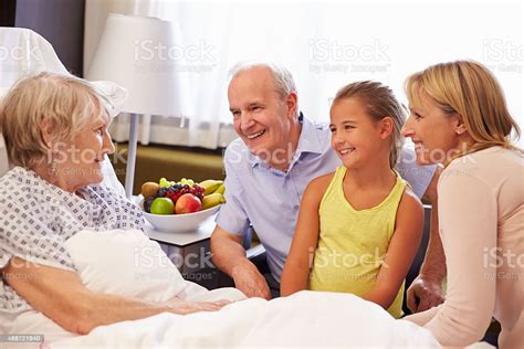 Family Visit To Grandmother In Hospital Bed Stock Photo - Download Image Now - iStock