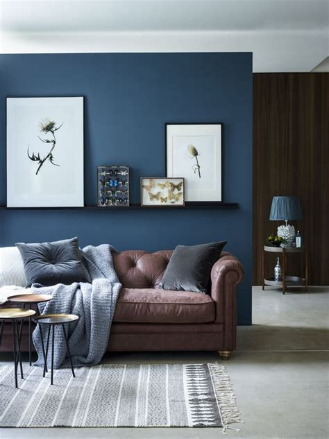 colours that go with brown sofa chic seating area with a brown sofa and a navy accent wall