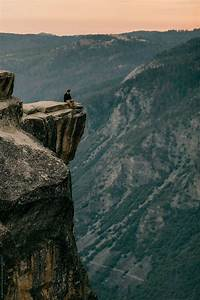 standing at the edge of a mountain cliff in yosemite