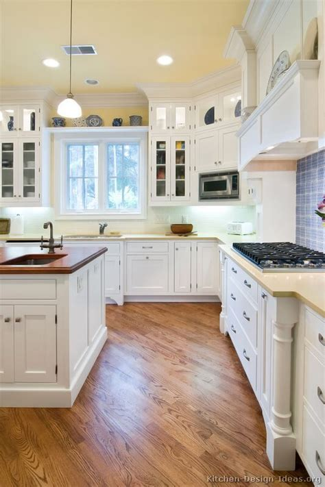 A Lovely Cottage Kitchen With White Cabinets, Wood Floors