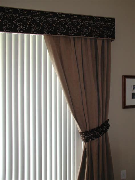 cornice with one way draw drapes and vertical blinds on