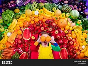 Little girl with variety of fruit and vegetable. Colorful ...