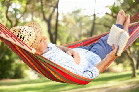Relaxing On Hammock by Senior Relaxing In Hammock With Book Stock Image