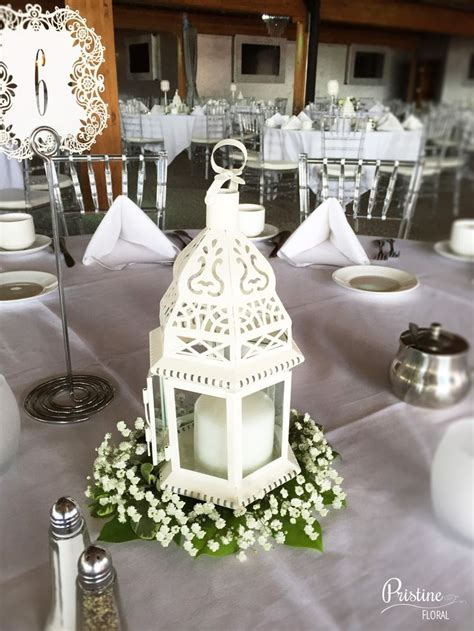 Lovely Lantern Centerpiece Finished With Greenery And Babys