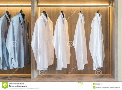 white  grey shirts hanging  wardrobe stock photo