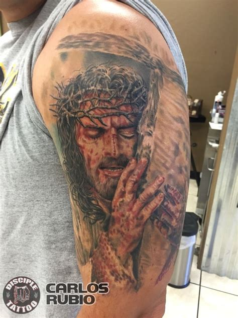 colored shoulder tattoo  dramatic jesus  cross