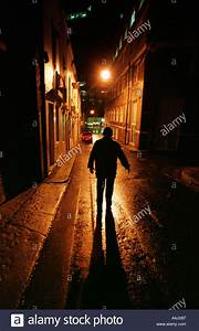 The dark shape of a man in a lonely city street at night ...