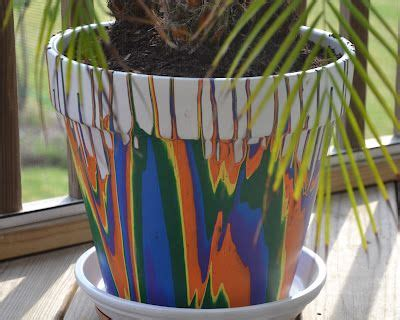 terra cotta pots sprayed white then acrylic paint is poured from the bottom the colors