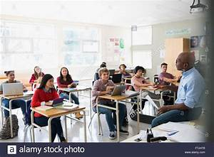 High school students listening to teacher in classroom ...