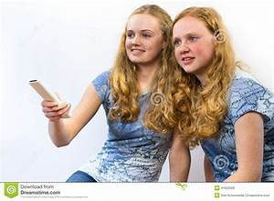 Two girls watching TV stock photo. Image of aiming, alike ...