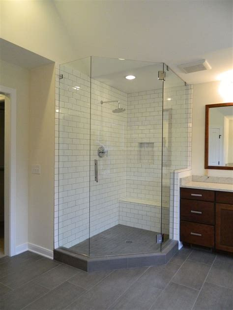 gray tile flooring with subway tile shower walls and bench