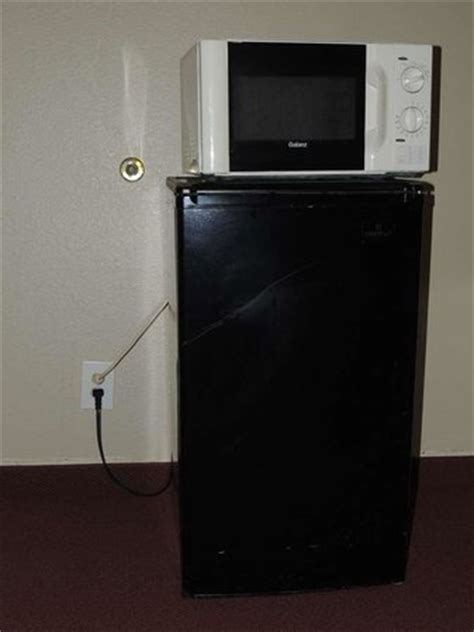 is it safe to put a microwave in a cabinet cockeyed microwave on top of tilted fridge picture of
