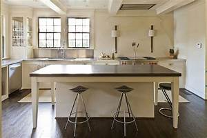 Cream kitchen island with black countertop transitional for Best brand of paint for kitchen cabinets with wall art iron work