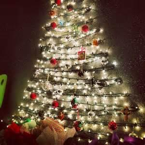 hang christmas lights on the wall and hook ornaments onto the lights diy christmas trees