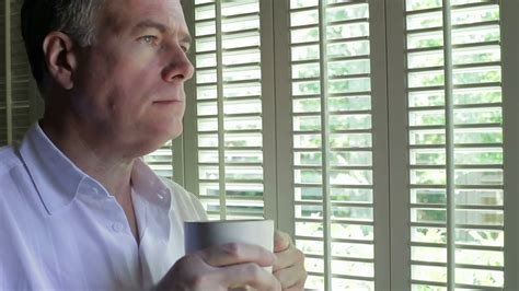 Man thinking with coffee while looking out a window Stock ...