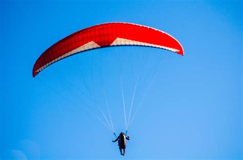 Person Using Red Parachute on Mid Air · Free Stock Photo
