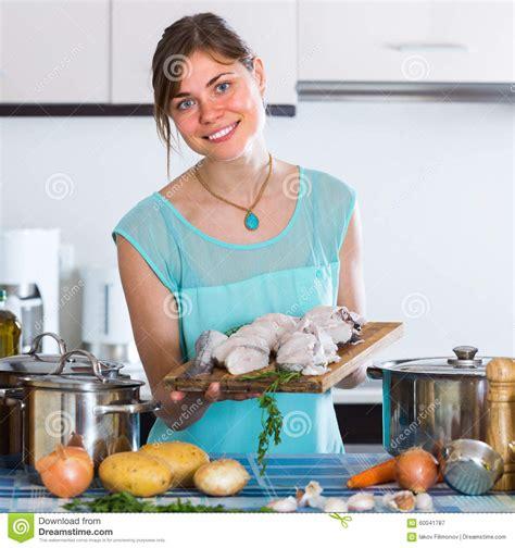 femme a la cuisine femme faisant cuire des poissons dans la cuisine photo