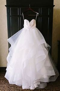 picture of wedding gown hanging in a contrasting backdrop With hanging wedding dress
