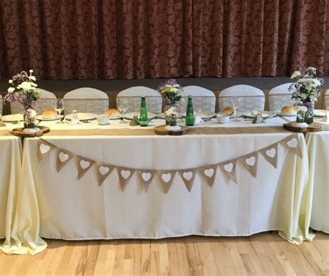rustic wedding with a top table decorated with ivory table cloths ivory chair covers with