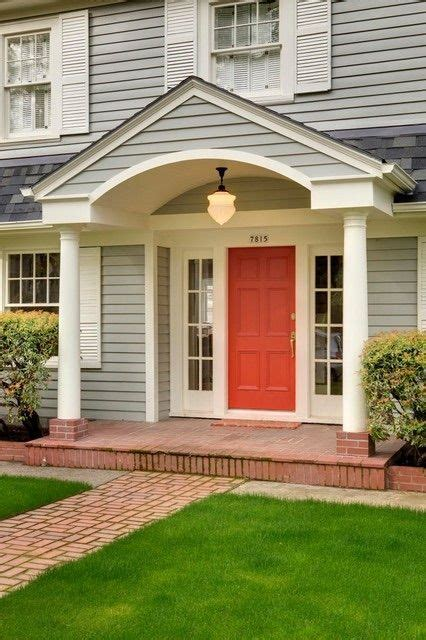 red orange door  light gray siding  white shutters arched portico brick colonial