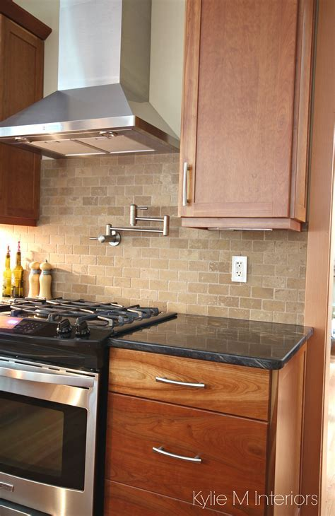 Natural cherry cabinets, travertine tile backsplash, black