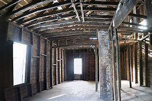 A Large  Gutted Room With Wooden Beams Exposed