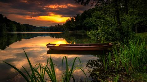 landscape nature sunset orange sky forest lake boat green