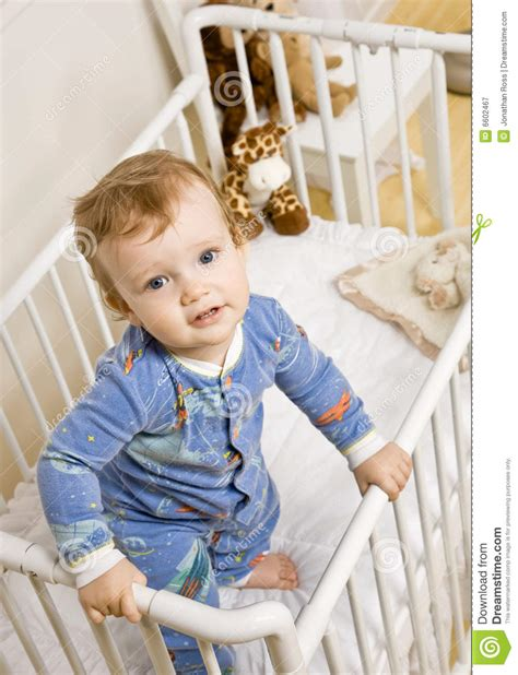 baby climbing out of crib toddler boy trying to climb out of crib stock image
