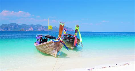 Thai Longtail Tourist Boats On White Sand Beach Of