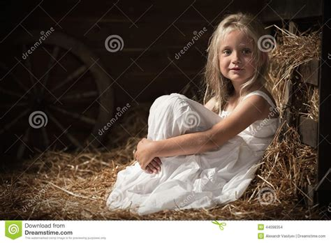 Girl Sits On Hay In The Barn Stock Photo
