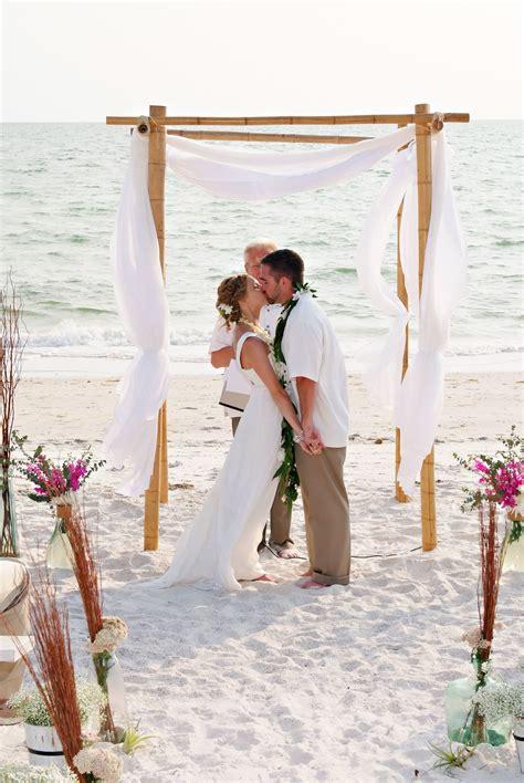 white fabric draped bamboo wedding arch