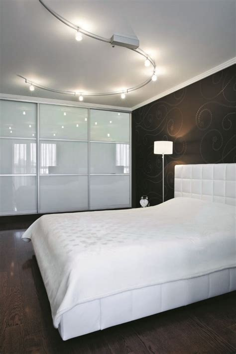 minimalist modern bedroom with track lighting fixtures over the bed with white bedding