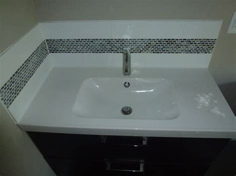 bathroom vanity with glass tile backsplash