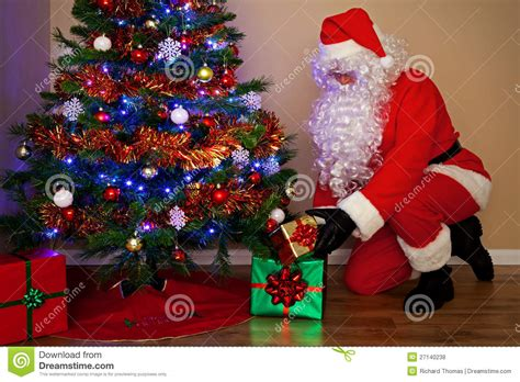 Santa Claus Delivering Presents Under The Tree. Stock