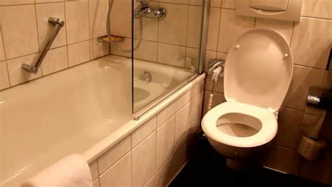 WC In White Toilet Is Installed. A Man Pushes A Button And