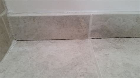 tiles for floor and wall insulation what do i use to fill in the crack between the wall and floor of my tiled bathrooms