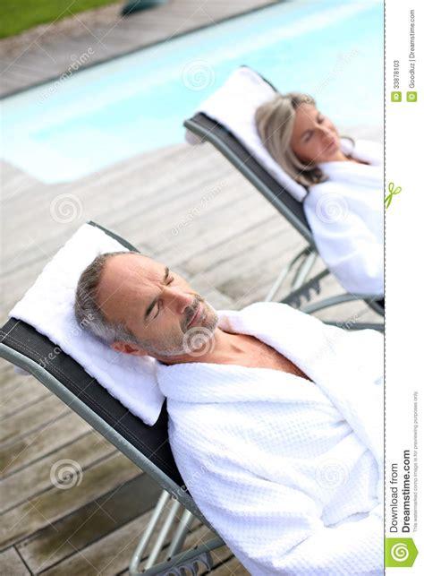 in white bathrobe relaxing near pool stock photos