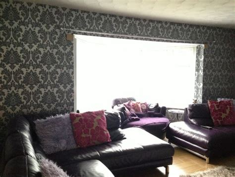 i grey silver damask wallpaper and plum leather sofas